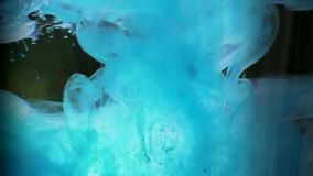 Blue paint hitting water. Inks in water and swirling in slow motion stock video footage