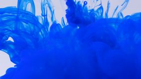 Blue paint ink falling in water creating abstract shapes and swirls background. Blue paint ink falling on water creating abstract shapes and swirls background stock video footage