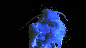 Blue paint in super slow motion splashing. Against a black background stock video footage