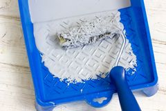 Blue paint tray with paint roller and paint inside it. Stock Photography