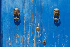 Blue painted aged wooden door with old bronze handles and locks in Rimini, Italy. Royalty Free Stock Photos