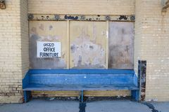Blue painted bench outside old abandoned warehouse in inner city. Old rustic faded blue painted bench outside abandoned brick factory in inner city royalty free stock image