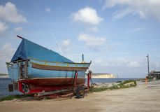 Moored boat on the harbourside in Malta. A blue painted boat, sitting on the harbourside, in a small fishing village in Malta stock images