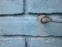 Blue painted brick wall with a pin and rusty iron wire stock photos