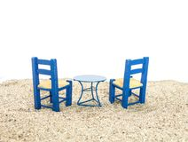 Blue painted chairs and table on sand, with white background. Blue painted chairs and table on sand, with white background Royalty Free Stock Photo