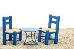 Blue painted chairs and table on sand, with white background. Blue painted chairs and table on sand, with white background Stock Images