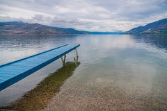Free Blue Painted Dock Extending Over Calm Lake With View Of Overcast Sky And Mountains Royalty Free Stock Images - 163937659