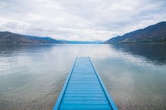 Free Blue Painted Dock On Lake With View Of Mountains And Cloudy Sky Royalty Free Stock Photography - 158100997