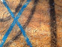 Blue painted letter X, black lines on the wooden bench. Blue letter X and black painted lines, graffiti, on the sharp, pressed wood on the bench, polished but stock image