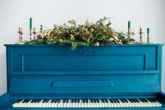 Blue painted old piano decorated with Christmas garland Royalty Free Stock Photo