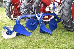 Blue painted plow. A blue painted restored plow is hitched to a red tractor Stock Photos