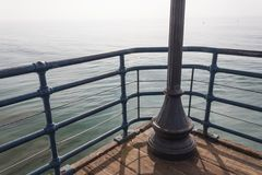 Blue painted railing and light post on the corner of a pier overlooking the ocean on a hazy day. Horizontal aspect Royalty Free Stock Images