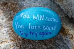 Blue painted rock stating You WIN some You Lose some Try try again royalty free stock images