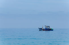 Blue painted small fishing boat in front of the Angolan coast. Of the Namib Desert. Dominating blue colors and calm mood Royalty Free Stock Photography