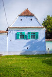 Blue painted traditional house with green windows from Viscri vi Royalty Free Stock Image