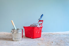 Blue painted wall with painting tools in front Royalty Free Stock Photography