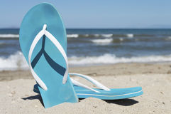 Blue pair of slippers on a sea shore with blue sea and sky in ba Royalty Free Stock Photos