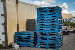 Blue palettes. Stacks of blue palettes beside a container Stock Photography