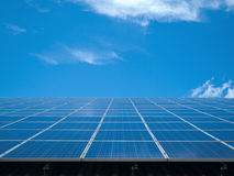 Blue panels for future. Closeup of a solarpanel with blue sky and white clouds in the background Stock Photography