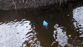 Blue paper boat of colored paper floats along the autumn stream. Blue paper boat of colored paper floats along autumn stream stock video
