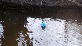 Blue paper boat of colored paper floats along the river bank. Blue paper boat of colored paper floats along river bank stock footage