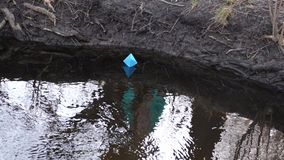 Blue paper boat of colored paper floats along the river bank. Blue paper boat of colored paper floats along river bank stock video