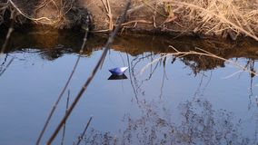 Blue paper boat sails along the river. Blue paper boat sails along river stock video