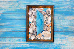 Blue paper boat and Sea shells in photo frame Royalty Free Stock Photography