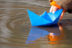 Blue paper boat in water in spring. Child's hand and blue paper boat in water in spring Stock Images