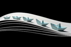 Paper blue boats on waves on a black background. A team of five blue paper boats in the dynamics on the waves and on a black background. 5 blue ships of royalty free stock photo