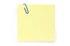 Blue paper clip with yellow notepaper Royalty Free Stock Photography