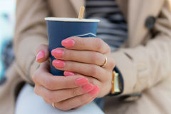 Blue paper Cup of coffee in female hands with pink manicure. The girl is dressed in a beige coat, striped t-shirt and blue jeans Stock Photos