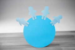 Blue paper cut out figures on globe Royalty Free Stock Images