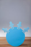 Blue paper cut-out people on the circle. Conceptual image of blue and paper cut-out people on the circle Stock Photos