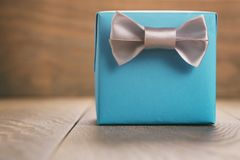 Blue paper gift box with silver ribbon bow on oak table Stock Image