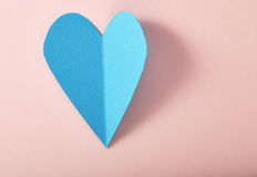 Blue paper heart on pink paper. Background royalty free stock photos