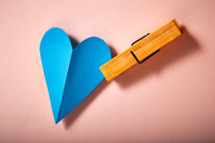 Blue paper heart on pink paper. Background stock image