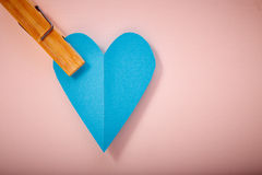 Blue paper heart on pink paper. Background stock photography