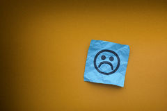 Blue paper note with sad face on a yellow paper background Stock Photography