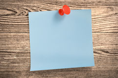 Blue paper note  on wood, clipping path. Royalty Free Stock Photo