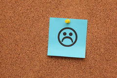 Blue paper with sad face on corkboard Stock Photo