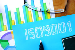 Blue paper with words iso 9001. Blue paper with words iso 9001 and glasses Royalty Free Stock Image