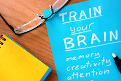 Blue paper with words  Train your Brain. Blue paper with words Train your Brain and glasses Stock Images