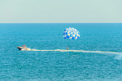 Blue parasail wing pulled by a boat in the sea water, Parasailin Royalty Free Stock Photography