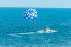 Blue parasail wing pulled by a boat in the sea water, Parasailin Royalty Free Stock Photo