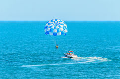 Blue parasail wing pulled by a boat in the sea water, Parasailing Royalty Free Stock Photo
