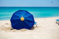 Blue parasol on sandy beach. With blue sea and a kite surf far in background Stock Images