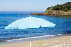 Blue parasol on sunny beach Stock Photo