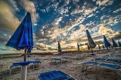 Blue parasols and beach chairs under a dramatic sky Royalty Free Stock Photo