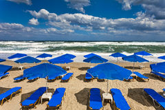 Blue parasols at an empty, stormy beach Royalty Free Stock Photography